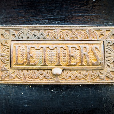 An antique letterbox in a black door